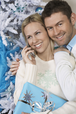 Woman using cell phone with man embracing her by Christmas tree Stock Photo - 3812464