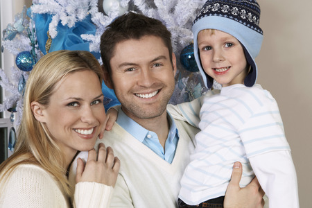 Couple with son (5-6) in front of Christmas tree, portrait Stock Photo - 3812398