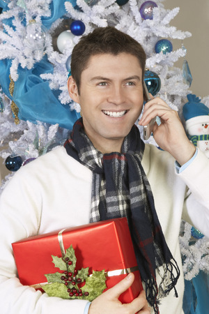 Man using cell phone holding present in front of Christmas tree Stock Photo - 3812347