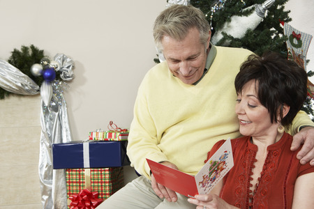 Senior couple looking at Christmas card in front of decorations Stock Photo - 3812627