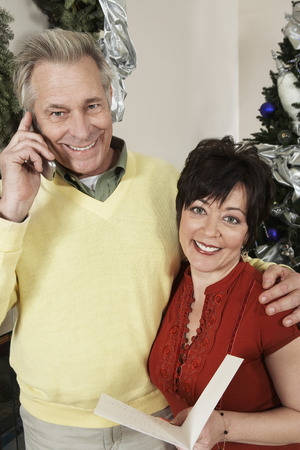 Senior couple holding greeting card, man on cell phone Stock Photo - 3812687