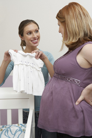 Two women looking at baby clothes by cradle Stock Photo - 3812200