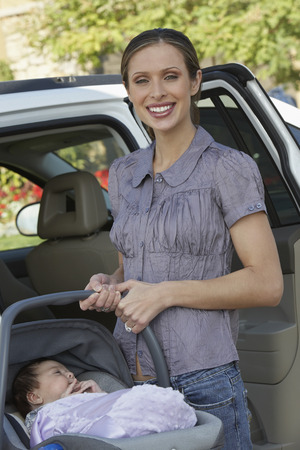 Portrait of woman with baby (1-6 months) in carrier by car Stock Photo - 3812455