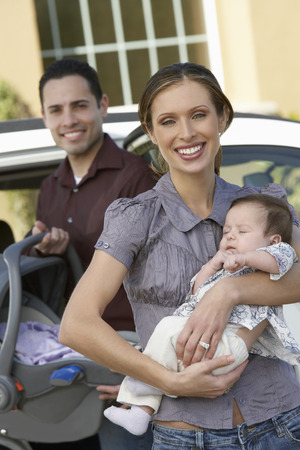 car carrier: Portrait of woman with baby (1-6 months) by car, man in background