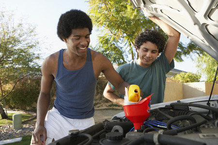 Two young men pouring oil into car engine Stock Photo - 3813198