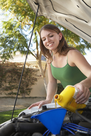 Young woman pouring oil into car engine Stock Photo - 3813131
