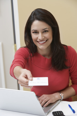 lap top: Business woman offering name tag in office, portrait LANG_EVOIMAGES