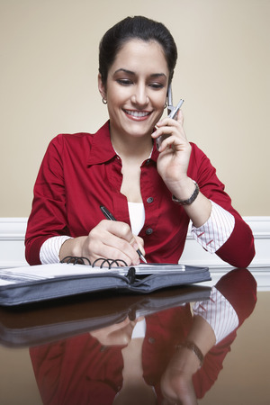 Business woman using mobile phone and writing in diary in office Stock Photo - 3811179