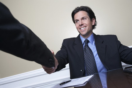 one person with others: Business man shaking hands with colleague at desk in office