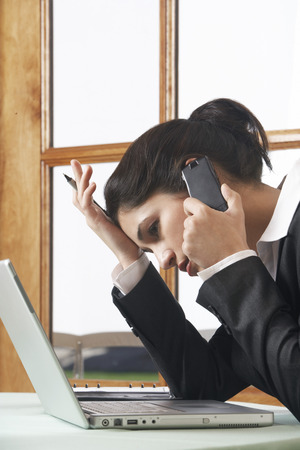 Business woman using mobile phone at desk in office Stock Photo - 3811132