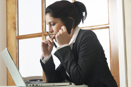 Business woman using mobile phone at desk in office Stock Photo - 3811186