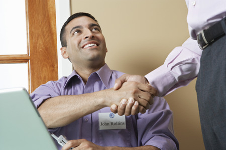 one on one meeting: Business man shaking hands with colleague at desk in office