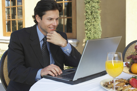 Mid adult business man working on laptop at outdoor cafe table Stock Photo - 3813206