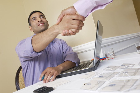 Two men shaking hands over desk with name tags Stock Photo - 3811259