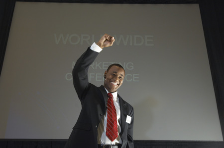 Business man speaking at conference, arm raised Stock Photo - 3811166