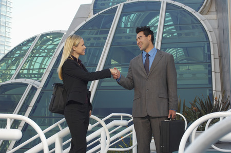 Businessman and woman shaking hands in front of office building Stock Photo - 3813181