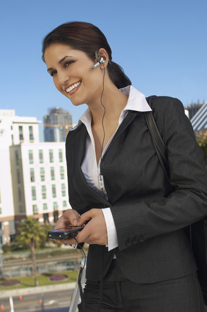 Businesswoman wearing headset, text messaging, outdoors Stock Photo - 3813173