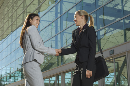 Two businesswomen shaking hands outside office building Stock Photo - 3813180