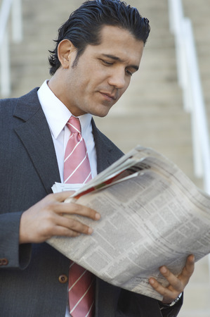 Businessman reading newspaper outdoors Stock Photo - 3813205