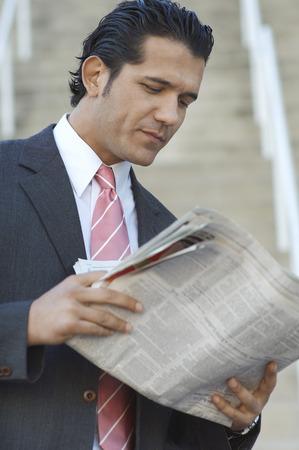 Businessman reading newspaper outdoors Stock Photo - 3813205