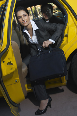 disembarking: Businesswoman getting out of taxi
