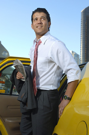 Businessman getting out of taxi Stock Photo - 3813194