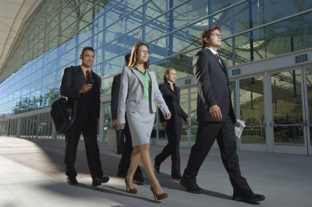 asian business women: Group of business people walking past office building LANG_EVOIMAGES