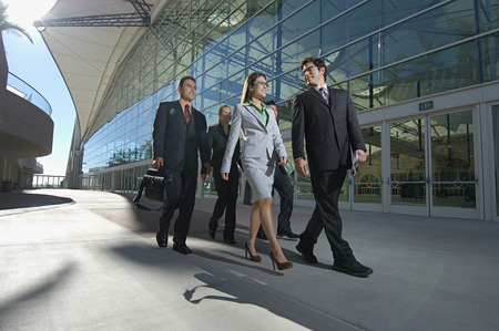business people walking: Group of business people walking past office building LANG_EVOIMAGES