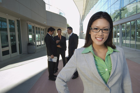 one person with others: Portrait of businesswoman in front of office building