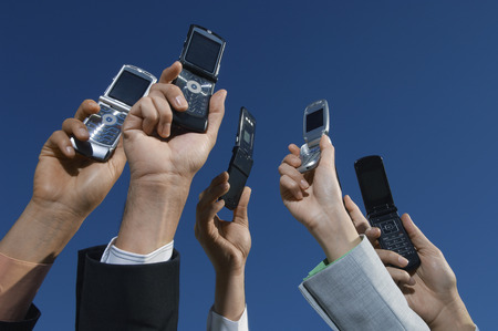 mobilephones: Business people holding mobile phones up in air, close-up of hands