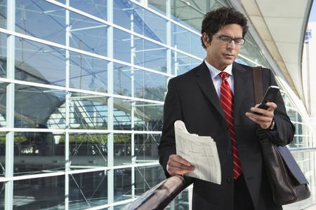 human pile: Uomo d'affari utilizzando telefoni cellulari al di fuori ufficio edificio