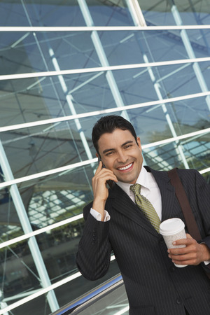 Businessman using mobile phone with take away coffee outside office building Stock Photo - 3811252