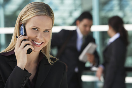 straight man: Businesswoman using mobile phone with colleagues in background, outdoors