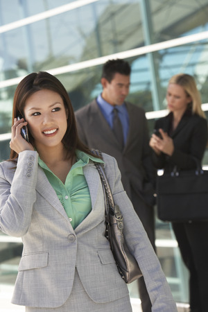 Businesswoman using mobile phone with colleagues in background, outdoors Stock Photo - 3811423
