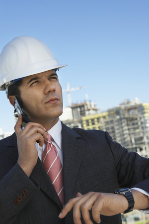 Businessman in hardhat using mobile phone, outdoors Stock Photo - 3811435