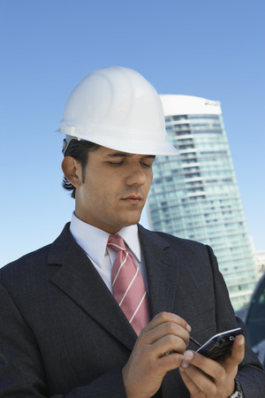 Businessman in hardhat using PDA outdoors Stock Photo - 3811407