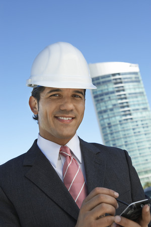 Businessman in hardhat using PDA outdoors, portrait Stock Photo - 3811401