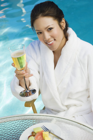 Young woman drinking champagne by swimming pool, portrait Stock Photo - 3811442