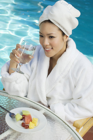 Young woman wearing bathrobe, drinking by swimming pool Stock Photo - 3811425