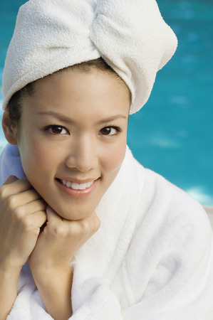 Young woman wearing bathrobe by swimming pool, portrait Stock Photo - 3811399
