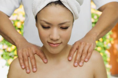 one person with others: Young woman having shoulder massage at health spa