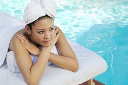 Young Chinese woman lying by swimming pool Stock Photo - 3811396