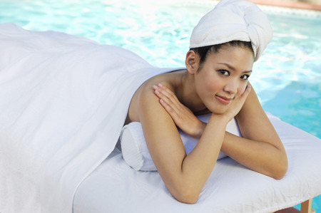 Young Chinese woman lying under towel by swimming pool, portrait Stock Photo - 3811333