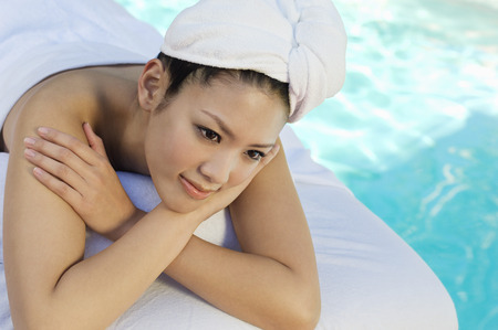 Young Chinese woman lying by swimming pool Stock Photo - 3811379