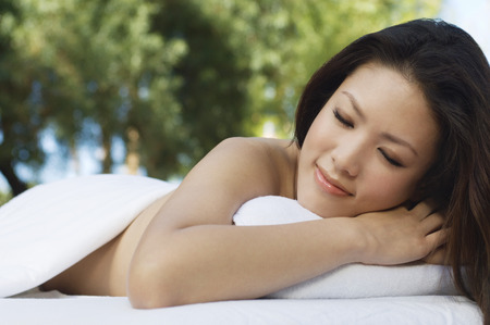 massage table: Young woman lying on massage table, outdoors