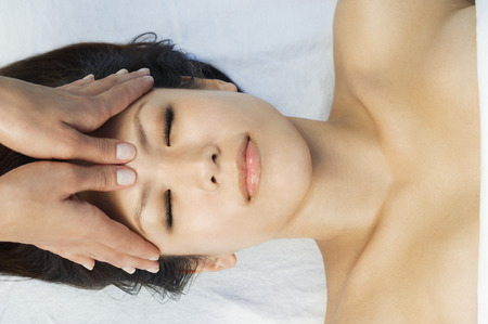 one person with others: Young woman having head massage at health spa