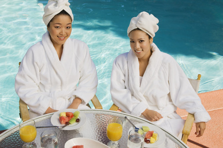 Two young women wearing bathrobes by swimming pool, portrait Stock Photo - 3811447