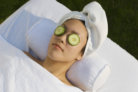 Young woman with cucumbers over eyes, lying on massage table outdoors Stock Photo - 3811373