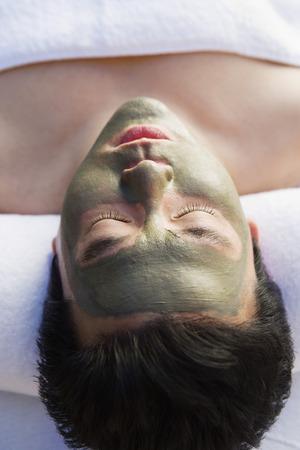 Young woman wearing mud facial mask at health spa, close-up Stock Photo - 3811357