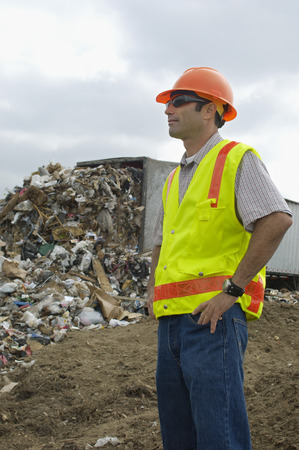 landfill site: Worker standing near truck dumping waste at landfill site